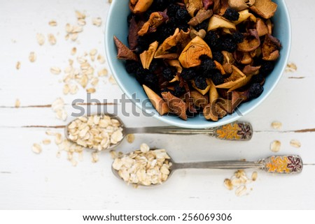 Two tablespoons of oatmeal lying on a white wooden background near blue plate with dried apples and berries. Healthy food. - stock photo