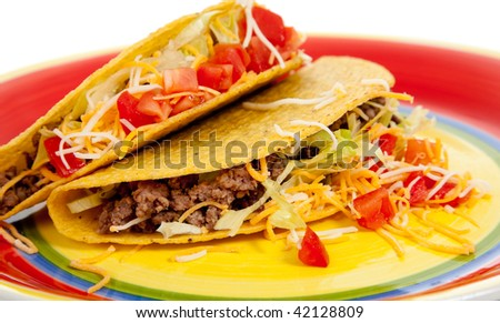Two tacos with beef, lettuce, tomato and cheese on a plate on white background - stock photo