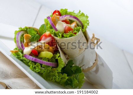 Two takeaway chicken tortillas with healthy salad ingredients bound in paper and stacked on a tray - stock photo