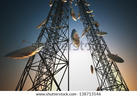 Two tall telecommunication towers with antennas in twilight sky. - stock photo