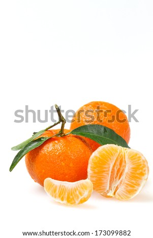 Two tangerines with a peel and one peeled on a white background - stock photo