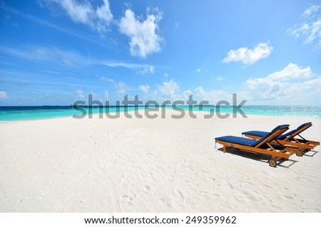 Two tanning beds on the tropical beach -- Concept of tropical vacations  - stock photo