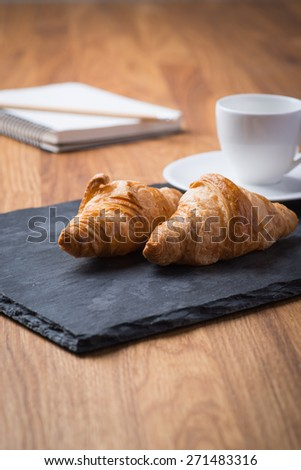 Two tasty and crusty french croissants with white cup of coffee and notebook on a wooden table - stock photo