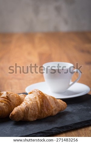 Two tasty and crusty french croissants with white cup of coffee on a wooden table - stock photo