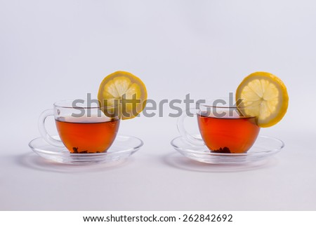 Two tasty cup of black leaf tea with lemon. - stock photo