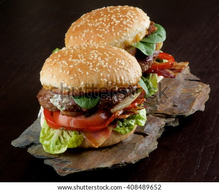 Two Tasty Hamburgers with Beef, Bacon, Lettuce, Tomatoes, Basil, Roasted Onion and Juicy Sauce on Sesame Buns on Stone Board closeup on Dark Wooden background - stock photo