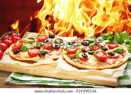 Two tasty pizzas with vegetables on fire flame background - stock photo