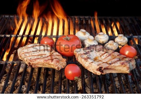 Two Tasty Rib Steaks, Vegetables, Tomato, Mushrooms Cooked Over Flaming Hot BBQ Grill. Summer Cookout or BBQ Party or Picnic Scene With Nobody. Black Background Isolated. - stock photo