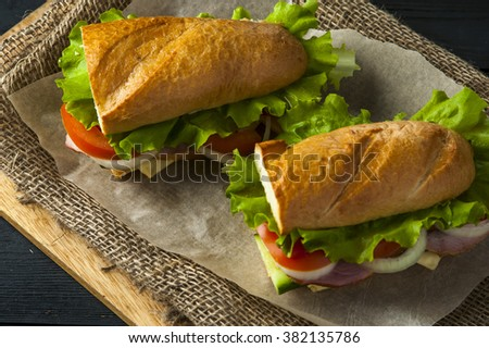 Two tasty sandwiches with ham, tomatoes, onion, cucumber and lettuce on baking paper. Fast food - stock photo