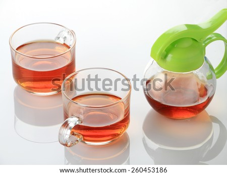 Two Tea Cup and Kettle in white reflective background - stock photo