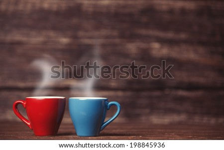 Two tea or coffee cup on wooden table. - stock photo