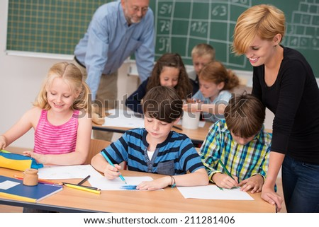 Two teachers in class with their young students with a beautiful young woman helping two small boys and a girl at a desk in the front with a male teacher working with another group behind