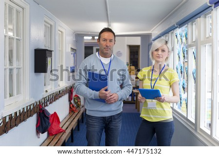 Two teachers standing in the corridor. They are holding a book and a digital tablet and looking at the camera. - stock photo