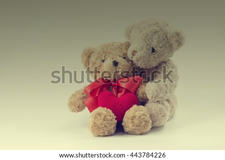Two teddy bears hugging with red heart yarn. image style vintage. - stock photo