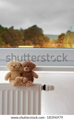 Two teddy bears on top of a radiator in front of a window. - stock photo
