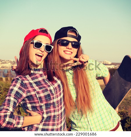 Two teen girl friends having fun together with skate board and colorful latex balloons. Outdoors, urban lifestyle. Photo toned style Instagram filters. - stock photo