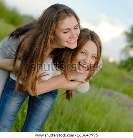 Two Teen Girl Friends Laughing in spring or summer outdoors - stock photo