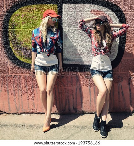 Two teen girl friends together having fun. Outdoors, urban lifestyle.  - stock photo