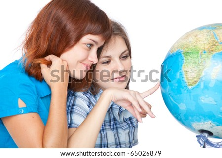 Two teen-girls are looking at globe. Isolated on white background - stock photo