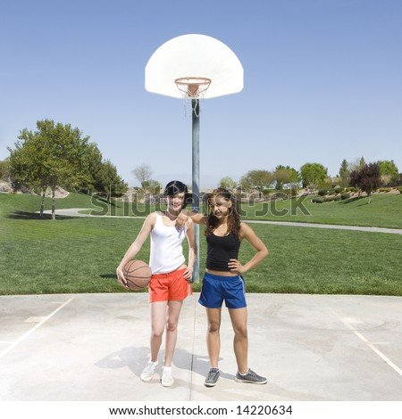 Two teen girls hang out at a basketball court in a park - stock photo