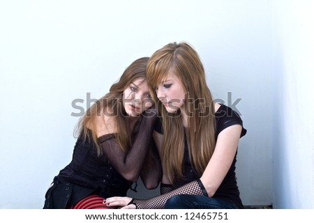 Two teen girls huddling together against a building, as if one is in emotional pain.