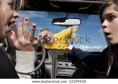 Two teen girls not knowing what to do after hitting a man because they were distracted by eachother in their car. - stock photo