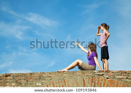 Two teen girls outdoors looking far away - stock photo