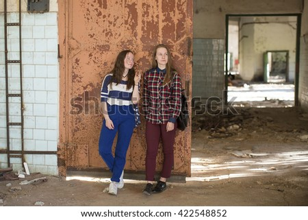 Two teen girls standing at the iron door in an abandoned building . - stock photo