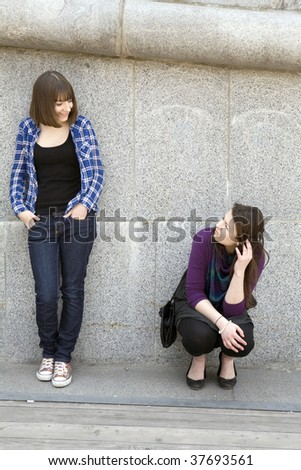 two teen girls standing at wall