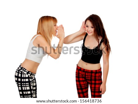 Two teen sisters whispering isolated on white background - stock photo