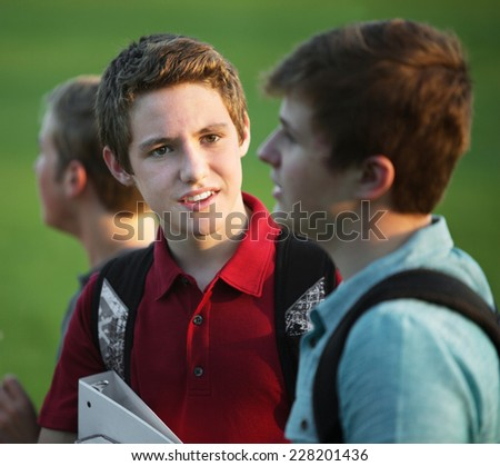 Two teen white male students talking outdoors