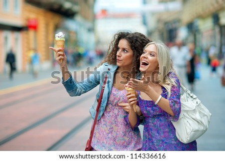 two teen woman friends having fun and eating ice cream