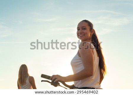 Two teenage biker girls on ride on sunny summer day, focus on brunette sporty beautiful young woman with bike looking back at camera with friendly smile, against blue sky - stock photo