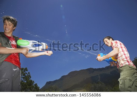 Two teenage boys fighting with water guns in mountains - stock photo