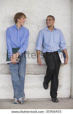 Two teenage boys holding books and talking while waiting for class. - stock photo