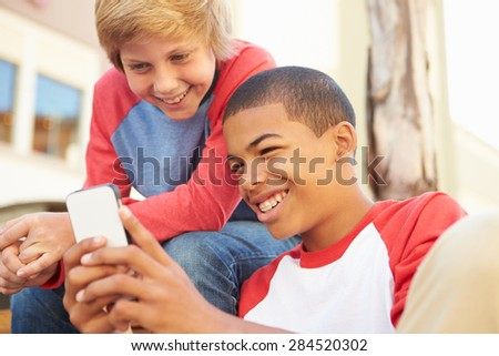 Two Teenage Boys Reading Text On Mobile Phone - stock photo