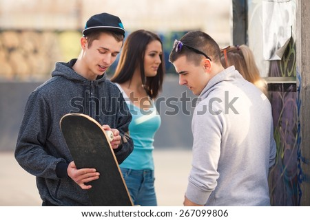 Two teenage boys talking about their skateboard and two girl talking in the background. - stock photo