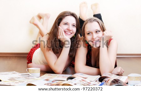 Two teenage girlfriends with fashion magazines lying on the floor - stock photo