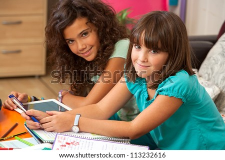 Two teenage girls doing homework at home. - stock photo