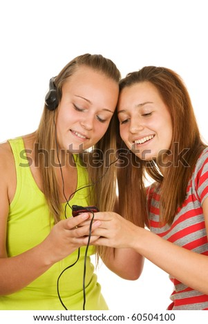 Two teenage girls listening to music on your mobile phone  isolated on white