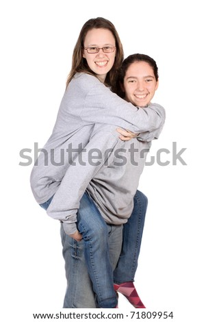 Two teenage girls playing around doing piggy back with one carrying the other