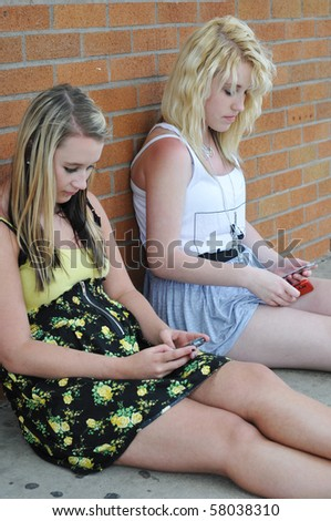 Two teenage girls sitting next to a brick wall texting on their mobile cellphones. - stock photo