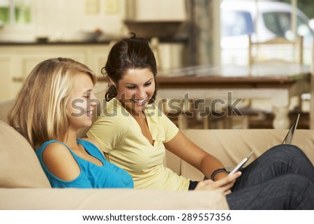 Two Teenage Girls Sitting On Sofa At Home Using Tablet Computer And Laptop - stock photo