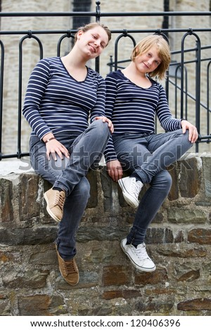 Two teenage girls sitting side by side, wearing the same dress and smiling - stock photo