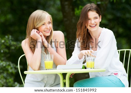 Two Teenage Girls Using Digital Tablet In Outdoor cafe