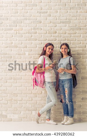 Two teenage girls with backpacks and in headphones are listening to music using smartphones and smiling, standing against white brick wall - stock photo