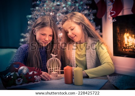 two teenage girls with christmas lights at home - stock photo
