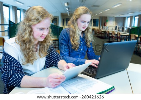 Two teenage girls working on computer and tablet in computer classroom - stock photo