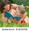 two teenage sisters having fun on green grass - stock photo