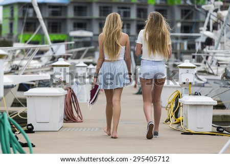 Two teenage sisters walk down a pier - stock photo